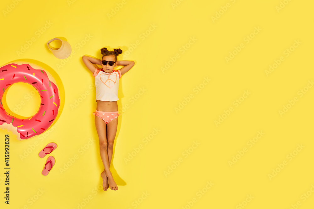 Fototapeta little child girl in swimwear and sunglasses lying on yellow background with inflatable rubber ring. Top view. copy space