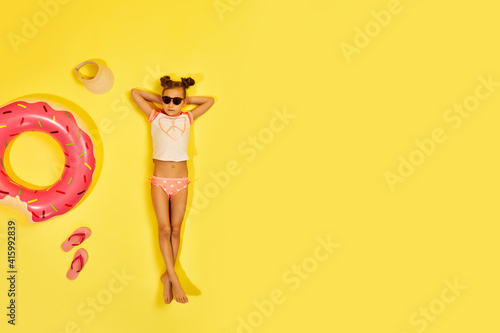 Fototapeta premium little child girl in swimwear and sunglasses lying on yellow background with inflatable rubber ring. Top view. copy space