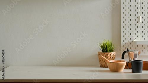 Fototapeta Home interior design with mixed bowl, coffee pot, mug, plant pot and copy space obraz
