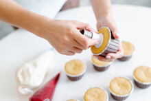 The Hands Of A Female Pastry Chef Hold A Cooking Bag And Fill The Red Berry Filling Cupcakes In A Wooden Tray.Food For Breakfast. Freshly Baked Cupcakes For Dessert. Foodies And Cuisine.