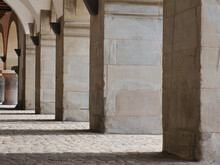View From The Side On Stone Columns At The Town Hall Of Lucerne, Switzerland, With Cobblestone Pavement