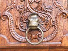 Door Knocker In The Shape Of A Lizard's Head On An Old Wooden Door With Decorations. Focus On The Door Knocker