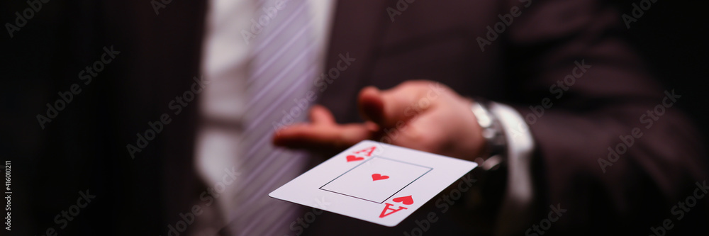 Fototapeta Man in business suit catche red ace playing card. Owning gambling business, maintaining casino and slot machine hall. Illusionist demonstrate trick.