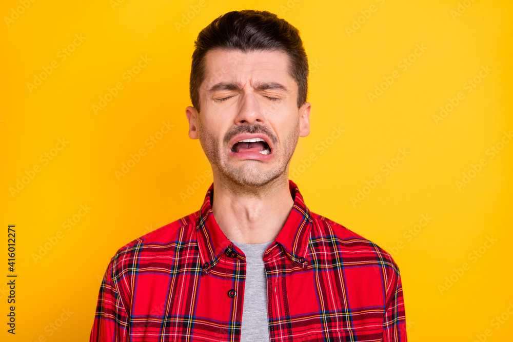 Fototapeta Photo of young handsome unhappy upset sad stressed depressed lonely man crying isolated on yellow color background