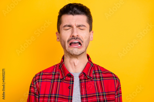 Fototapeta Photo of young handsome unhappy upset sad stressed depressed lonely man crying isolated on yellow color background obraz