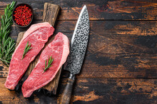 Raw Beef Meat Cap Sirloin Steak On A Cutting Board. Dark Wooden Background. Top View. Copy Space