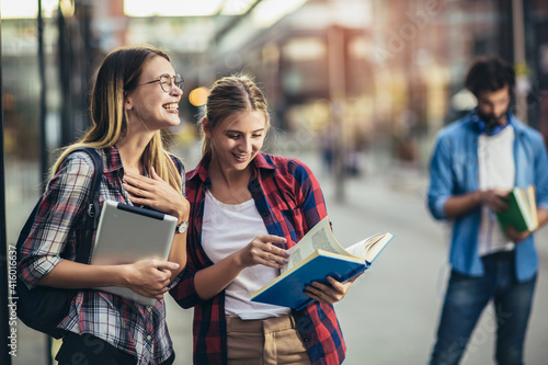 Happy young university students friends studying with books and digital tablet at university