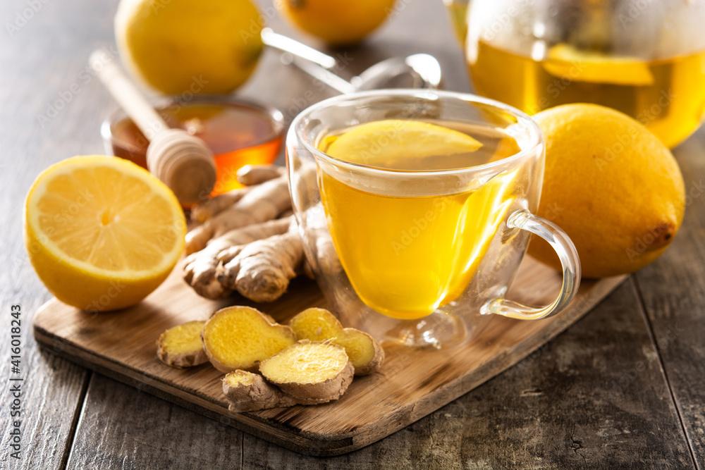 Fototapeta Ginger tea with lemon and honey in crystal glass on wooden table