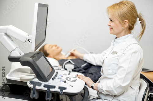 Fototapeta Doctor examining thyroid of female patient with ultrasound scan in medical clinic. Health and wellness concept. obraz
