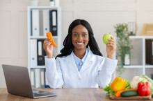 Happy Female Dietitian Holding Apple And Carrot At Medical Weight Loss Clinic