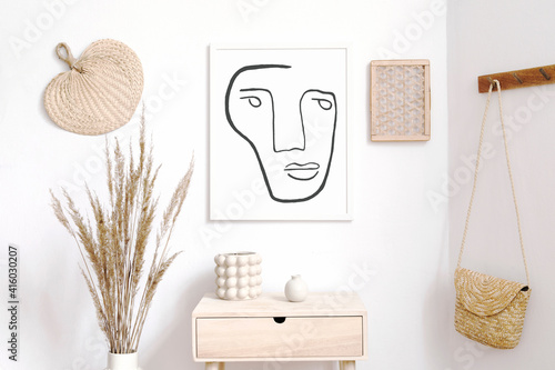 Stylish neutral interior of living room with white mock up poster frame, elegant rattan accessories, wooden shelf, hanging hat and tropical palm leafs. Minimalistic concept of home decor. Template. © FollowTheFlow