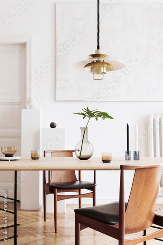 Stylish and modern dining room interior with design sharing table, chairs, gold pendant lamp, abstract paintings and elegant accessories. Tropical leafs in vase. Eclectic home decor.