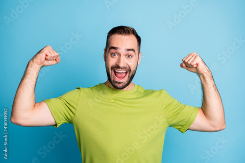 Photo of excited crazy strong man show raise hands biceps cheerful mood isolated Fotobehang