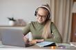 Smiling teen girl in wireless headset having online lesson