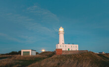 The Moon Sets Over The Lighthouse At Dawn, Flamborough, Yorkshire, UK.