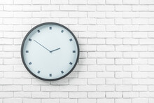 White Round Wall Clock In Black Frame On The Left Side Of Light Brick Wall