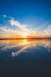 波の水たまりに反射した夕日と空と雲