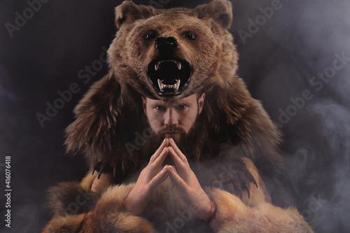 Magic fighting shaman werewolf man with a beard in a fur dress in a dark room Fototapeta
