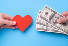 Male Hand Gives 300 Dollars To Female Hand With Red Heart, Blue Background
