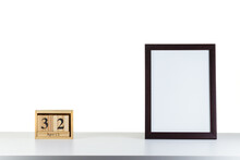 Wooden Calendar 32 April With Frame For Photo On White Table And Background