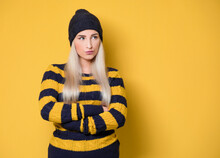 Annoyed Young Woman, Model Wearing Woolen Cap And Sweater, Isolated On Yellow Background. Displeased Girl With Arms Crossed