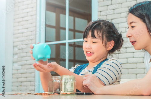 Fototapeta Asian mother is teaching her daugther about financial saving and money management using piggy bank and saving jar. obraz