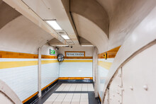 London, UK Tube Station Underground Corridor Hallway With Nobody And Sign Direction For To The Trains With Yellow Orange Colors