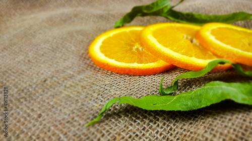 Świeży, soczysty plasterek pomarańczy i zielony liść. - fototapety na wymiar