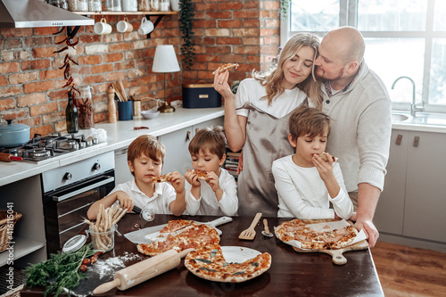 Obraz na plátně Warm portrait of a happy and young family they taste a domestic pizza