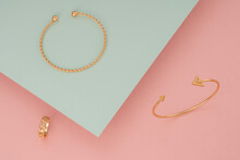 Top View Of Golden Bracelets And Ring On Pink And Green Background