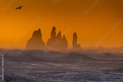View from cape Dyrholaey on Reynisfjara Beach and Reynisdrangar basalt sea stacks, Iceland. Stormy sunrise