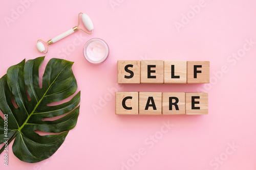 Obraz na plátně SELF CARE - text on wooden cubes on pink background