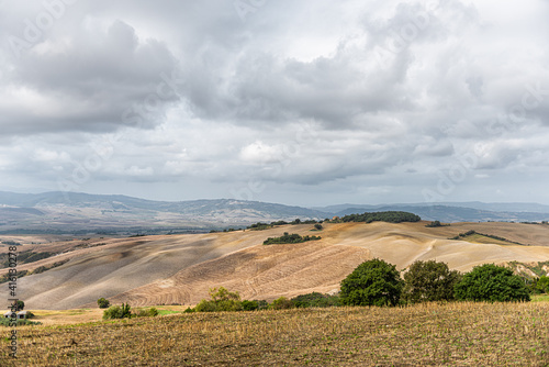 Fototapeta premium Val D'Orcia countryside hills in Tuscany, Italy with rolling plowed brown scenery and villas with farm landscape idyllic picturesque meadow fields