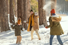 Cheerful Young Man, His Wife And Little Daughter In Winterwear Playing Snowballs
