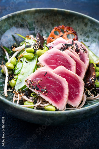 Modern style traditional Japanese gourmet seared tuna fish steak tataki with soba noodles and stir-fried vegetables served as close-up on a Nordic design bowl