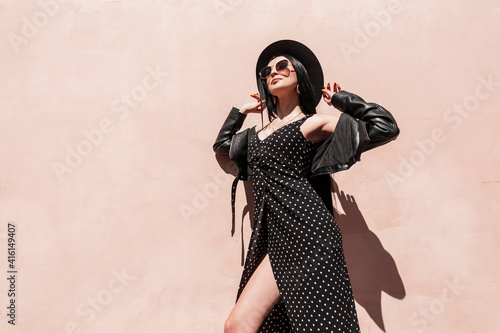 Obraz Fashion glamorous young woman in stylish sunglasses in leather jacket in beautiful dress straightens hat on sunny day. Lovely trendy girl in elegant black summer clothes enjoys sunlight outdoors. - fototapety do salonu