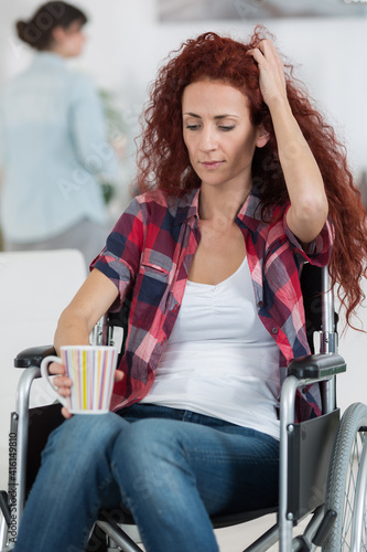 Foto cheerful crippled lady on wheelchair with cup of tea