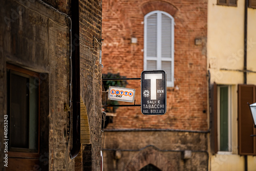 Fototapeta premium Siena, Italy - August 27, 2018: Alley street in historic medieval old town village in Tuscany with sign for lotto lottery and sali e tabacchi