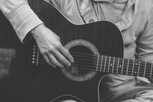 Black And White Photo Of A Musician Playing The Guitar. Fingers Touch The Strings Close-up