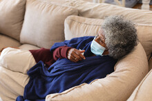 Sick African American Senior Woman Wearing Face Mask Lying On The Couch