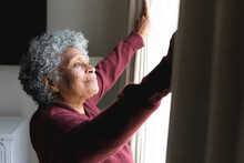 Thoughtful African American Senior Woman Opening Window Curtains At Home
