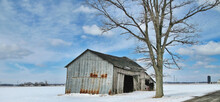 An Old Gray Barn Starting To Fall Down After Years Of Use In The Snow With A Beautiful Blue Sky In The Background.