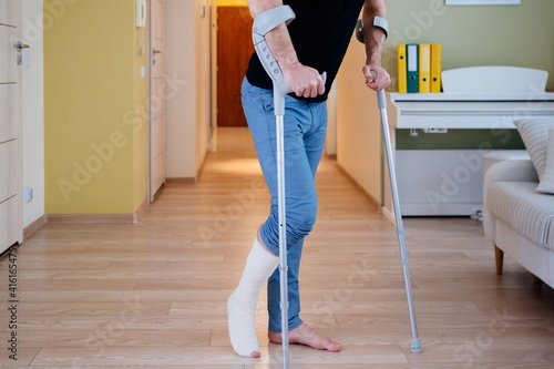 Injured man trying to walk on crutches. Close-up mid section of a man with crutches. © Daniel Jędzura