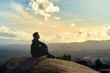 Young Boy Sitting On Top Of A Mountain Looking To The Horizon. Enterprising Man Sitting On A Rock With Background Sunset Landscape. Dark Teenager With Latino Features On A Mountain