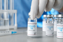 Doctor Taking Glass Vial With COVID-19 Vaccine From  Table, Closeup