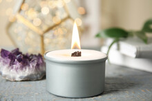 Burning Candle With Wooden Wick On Grey Table