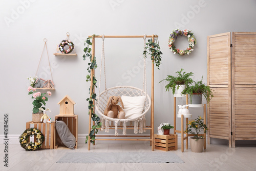 Easter photo zone with floral decor and swing chair indoors