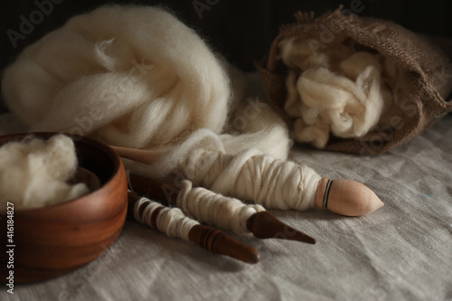 Fototapeta premium Soft white wool and spindles on table, closeup