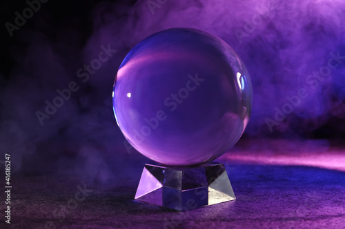 Papel de parede Crystal ball on table and smoke against dark background