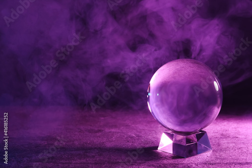 Tela Crystal ball on table and smoke against dark background, space for text